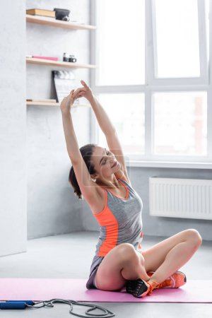 Sportswoman with crossed legs stretching on fitness mat near skipping rope