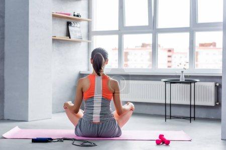 Photo pour Vue arrière de la femme assise avec les jambes croisées près de corde sautante et haltères - image libre de droit