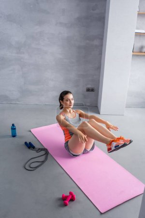 Photo for Sportswoman doing abs on fitness mat near sport equipment and sports bottle - Royalty Free Image