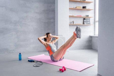 Photo pour Sportswoman avec les jambes tendues faisant abdos sur tapis de fitness près de l'équipement sportif - image libre de droit