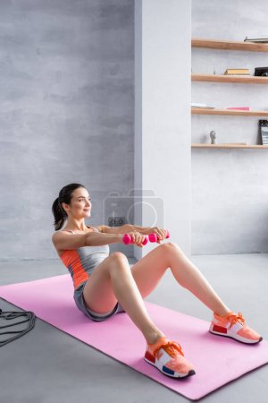Photo for Young adult woman with dumbbells doing abs on fitness mat at home - Royalty Free Image