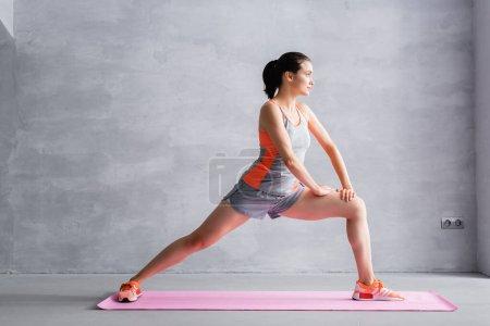 Photo pour Vue latérale de la sportive regardant loin et faisant fente sur tapis de fitness - image libre de droit