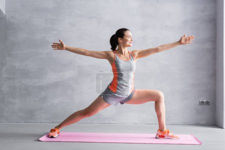 Sportswoman with outstretched hands doing lunge on fitness mat