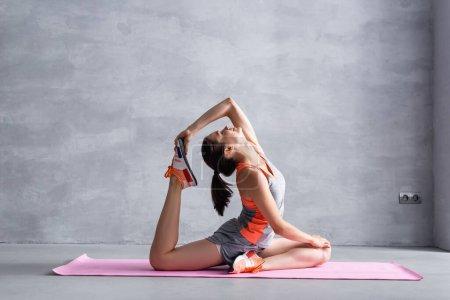 Foto de Vista lateral del entrenamiento de la mujer en la esterilla de fitness sobre fondo gris - Imagen libre de derechos