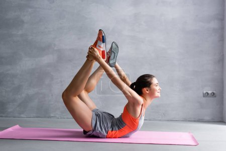 Photo for Side view of sportswoman training on fitness mat on grey background - Royalty Free Image