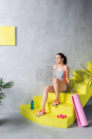 Photo pour Sportswoman assis sur les escaliers près de la bouteille, haltères et tapis de fitness à la maison - image libre de droit