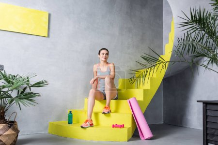 Sportswoman looking away and sitting on stairs near sport equipment