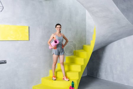 Young sportswoman holding fitness mat while looking at camera on stairs at home
