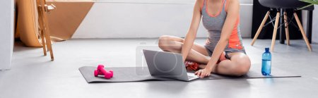 Panoramic shot of young woman using laptop on fitness mat at home