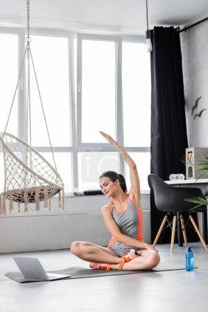 Foto de Enfoque selectivo de la deportista que se calienta mientras entrena cerca de la computadora portátil y la botella de agua en la alfombra de fitness - Imagen libre de derechos