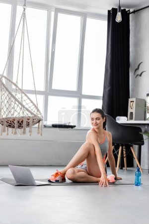 Selective focus of young sportswoman exercising while looking at laptop near bottle of water at home