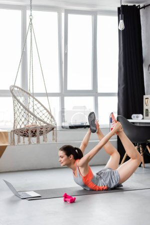 Photo for Sportswoman training near laptop and dumbbells on fitness mat in living room - Royalty Free Image