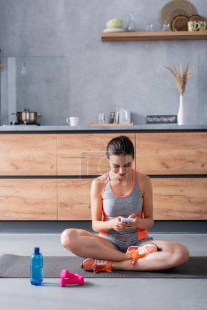 Photo pour Sportswoman utilisant smartphone sur tapis de fitness près des haltères et bouteille d'eau à la maison - image libre de droit