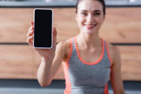 Selective focus of sportswoman showing smartphone with blank screen at home