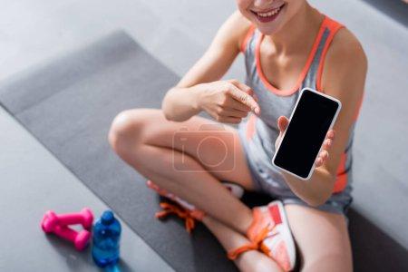 Foto de Vista recortada de la mujer en ropa deportiva apuntando al teléfono inteligente con pantalla en blanco en la estera de fitness - Imagen libre de derechos