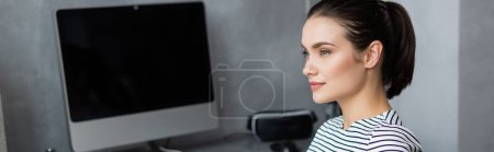 Photo for Panoramic shot of freelancer looking away near computer monitor at home - Royalty Free Image