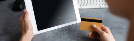 Website header of freelancer holding digital tablet and credit card while working at home