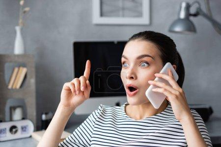 Emocionado freelancer tener idea mientras habla en el teléfono inteligente en casa