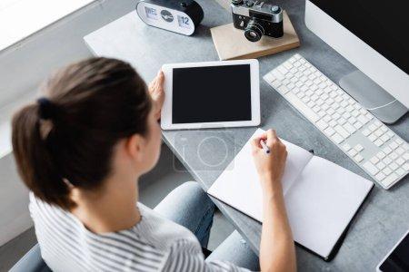 Vue aérienne de l'écriture freelance sur ordinateur portable tout en tenant tablette numérique à table