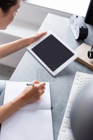 Photo pour Concentration sélective du télétravailleur utilisant une tablette numérique tout en écrivant sur un ordinateur portable à la maison - image libre de droit