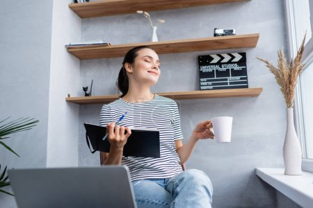 Photo for Selective focus of freelancer with closed eyes holding cup and notebook near laptop in living room - Royalty Free Image