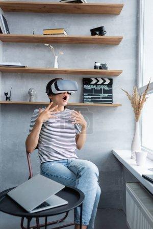 Foto de Enfoque selectivo de la mujer sorprendida en auriculares vr sentado cerca de la computadora portátil en la mesa de café en la sala de estar - Imagen libre de derechos