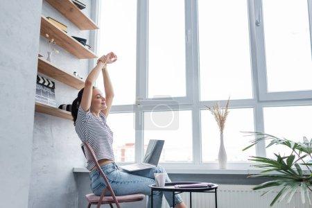 Photo pour Jeune femme étirant près d'un ordinateur portable, tasse et ordinateur portable à la maison - image libre de droit