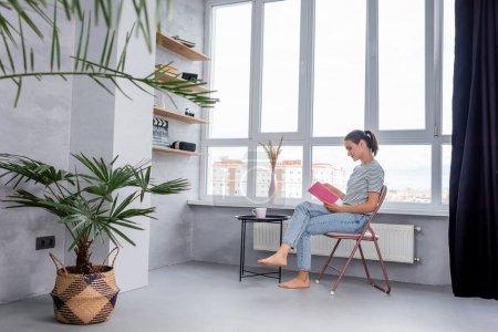 Selektiver Fokus der barfüßigen Frau, die Buch neben Tasse auf Couchtisch zu Hause liest