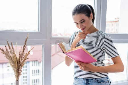 Young woman reading book near window at home