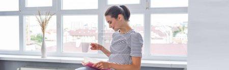 Photo pour Culture horizontale de femme avec livre de lecture de tasse près de la fenêtre à la maison - image libre de droit