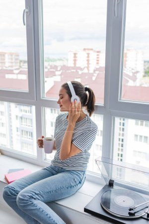 Selective focus of woman listening music in headphones while holding cup near vinyl player on windowsill