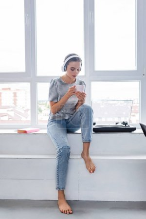 Photo pour Femme pieds nus dans un casque tenant tasse tout en étant assis près du livre et lecteur de vinyle sur le rebord de la fenêtre - image libre de droit
