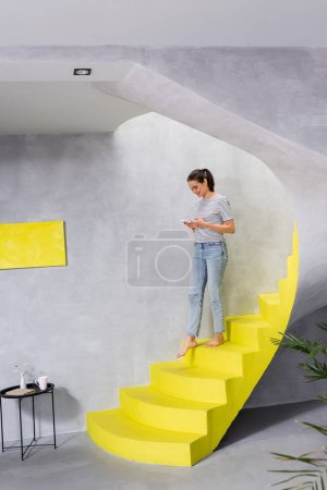 Selective focus of barefoot woman with smartphone walking on stairs at home