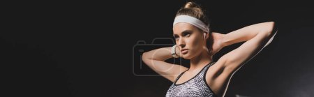 Panoramic shot of sportswoman with hands behind head on black background