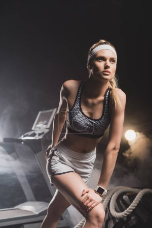 Photo for Sportswoman getting ready to run near treadmill in gym - Royalty Free Image