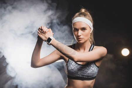Front view of sportswoman with clenched hands with smoke on background