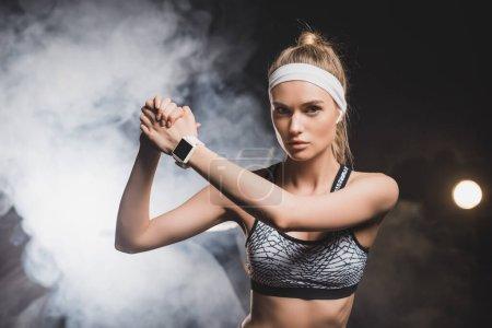 Photo pour Vue de face de la sportive avec les mains serrées avec de la fumée sur le fond - image libre de droit