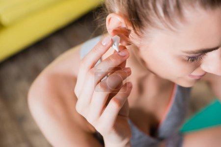 Foto de Vista recortada de mujer joven con auriculares inalámbricos - Imagen libre de derechos
