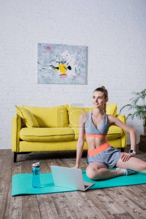 Photo pour Sportswoman assis sur tapis de fitness près d'un ordinateur portable et bouteille de sport à la maison - image libre de droit