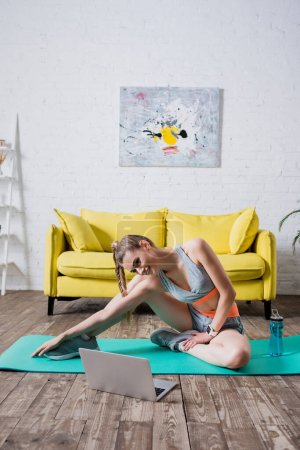 Sportlerin streckt sich neben Laptop und Sportflasche auf Fitnessmatte