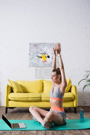 Photo for Sportswoman with hands in air sitting near laptop on fitness mat at home - Royalty Free Image