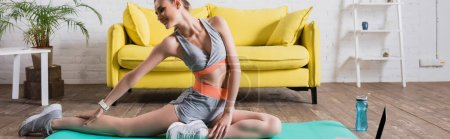 Photo for Panoramic shot of sportswoman training on fitness mat near sports bottle at home - Royalty Free Image