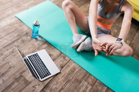 Photo for Cropped view of sportswoman stretching near laptop and sports bottle at home - Royalty Free Image