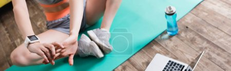Photo for Panoramic shot of sportswoman stretching near laptop and sports bottle at home - Royalty Free Image