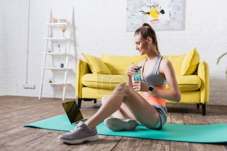 Photo for Smiling sportswoman holding sports bottle while sitting on fitness mat at home - Royalty Free Image