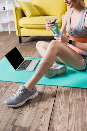 Photo for Cropped view of smiling sportswoman holding sports bottle near laptop at home - Royalty Free Image