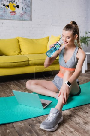 Photo for Selective focus of smiling sportswoman holding sports bottle and looking at laptop on fitness mat at home - Royalty Free Image