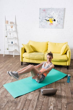 Young sportswoman exercising on fitness mat near laptop and sports bottle at home