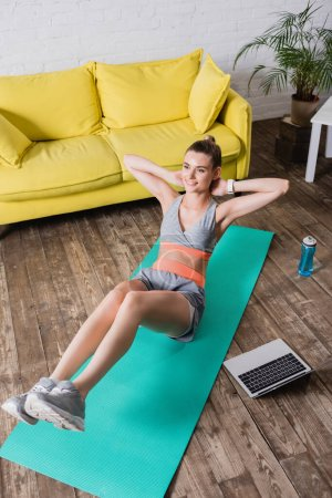 Photo pour Vue en angle élevé de la sportive gaie travaillant sur tapis de fitness près d'un ordinateur portable et bouteille de sport à la maison - image libre de droit