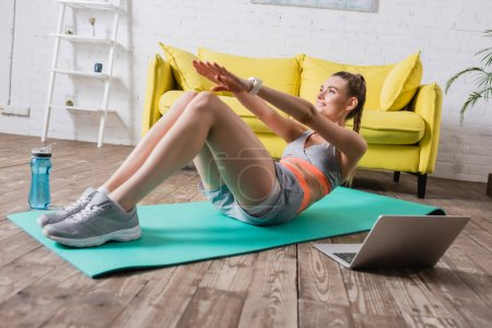 Photo for Selective focus of smiling sportswoman training on fitness mat near sports bottle and laptop - Royalty Free Image